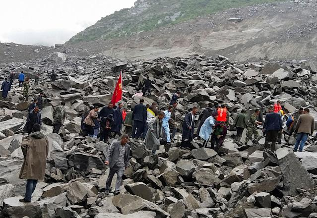 <p>People search for survivors at the site of a landslide that destroyed some 40 households, where more than 100 people are feared to be buried, according to local media reports, in Xinmo Village, China, June 24, 2017. (Photo: Stringer/Reuters) </p>