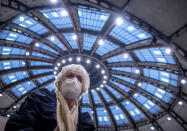 After receiving her vaccination against the novel coronavirus, 90-year-old Odores H. sits under the domed roof of the vaccination centre in the Festhalle in Frankfurt, Germany, Tuesday, Jan.19, 2021. This is where thousands of people usually gather for concerts and trade fairs, and where the state of Hesse operates one of its vaccination centers. (Boris Roessler/dpa via AP)