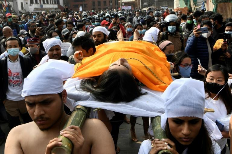 Demonstrators in Kathmandu dressed in white mourning carry a young woman on a stretcher to symbolise the victims of raped and murder in Nepal