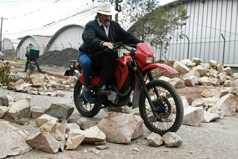 Former Honduran President Manuel Zelaya, ousted in a 2009 coup, rides a motorcycle through the blocked streets and avenues of Tegucigalpa