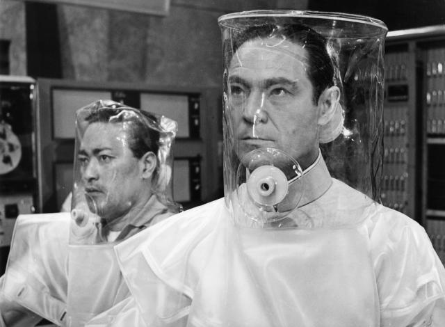 Anthony Chinn and Joseph Wiseman wearing decontamination suits in a scene from the film 'Doctor No', 1962. (Photo by United Artists/Getty Images)