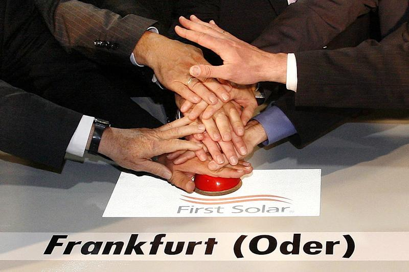 FILE - In this July 9, 2007 file photo hands push a red button for the symbolic start of a solar plant of the US company First Solar in Frankfurt/Oder, eastern Germany. First Solar Inc. says it's shuttering its manufacturing operations at Frankfurt an der Oder in Germany due to deteriorating market conditions in Europe and to reduce costs. The Tempe, Arizona-based company said Tuesday, April 17, 2012 it will also indefinitely idle four production lines in Malaysia. (AP Photo/dapd, Michael Urban, File)