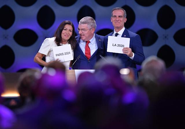International Olympic Committee President Thomas Bach (C) poses for pictures with Paris Mayor Anne Hidalgo (L) and Los Angeles Mayor Eric Garcetti on September 13, 2017 (AFP Photo/Fabrice COFFRINI)