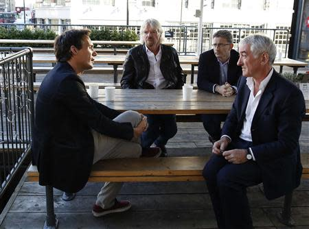 Sir Richard Branson, Founder of Virgin Group, centre, with Richard Reed, Co-Founder of Innocent Drinks, L, Kevin Horne, Chairman of the Cavendish Consortium, R, and Sir Tom Shebbeare, Chairman of Virgin StartUp, far R, have coffee before a seminar about the Virgin StartUp scheme for young entrepreneurs at Box Park in east London, October 24, 2013. REUTERS/Olivia Harris