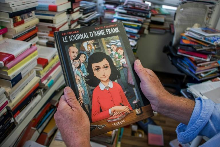 "A man holds a copy of the graphic novel version of ""The Diary of Anne Frank"", by Israeli writer-director Ari Folman and illustrator David Polonsky, in Paris on September 18, 2017"