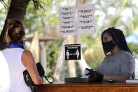 FILE - In this June 1, 2020 file photo, Nailea Rosales works behind a protective shield wearing a protective mask and gloves at the Morada Bay Beach Cafe in Islamorada, in the Florida Keys, during the new coronavirus pandemic. Repealing statewide mask mandates and criticizing the Biden administration's unemployment-based formula for distributing billions in federal aid has put Republican governors and their approach to handling the coronavirus pandemic back in the spotlight. (AP Photo/Lynne Sladky, File)