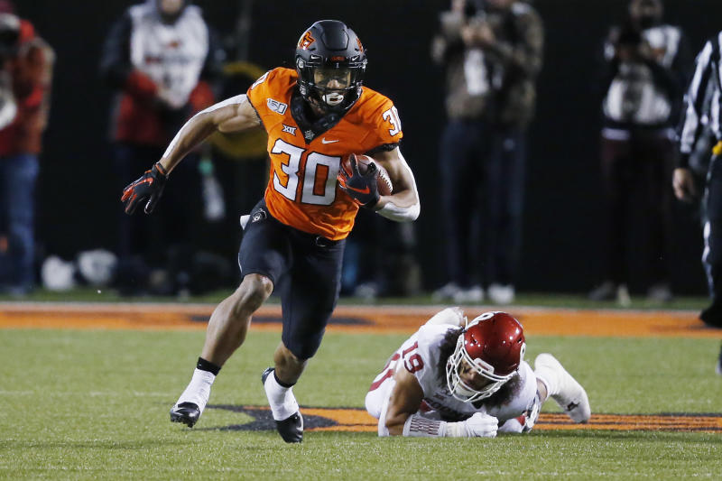 Oklahoma State running back Chuba Hubbard (30) carries past Oklahoma linebacker Caleb Kelly (19) during an NCAA college football game in Stillwater, Okla., Saturday, Nov. 30, 2019. (AP Photo/Sue Ogrocki)