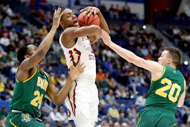 <p>Trent Forrest #3 of the Florida State Seminoles is fouled between Ben Shungu #24 and Ernie Duncan #20 of the Vermont Catamounts during their first round game of the 2019 NCAA Men's Basketball Tournament at XL Center on March 21, 2019 in Hartford, Connecticut. (Photo by Rob Carr/Getty Images) </p>