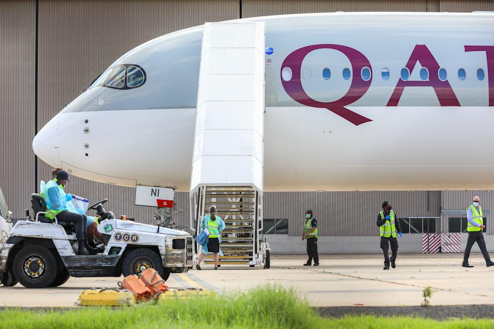 Biosecurity and airport staff in PPE and masks surround a chartered flight at Melbourne carrying players and staff for the Australian Open tennis tournament. (Photo: Asanka Ratnayake via Getty Images)