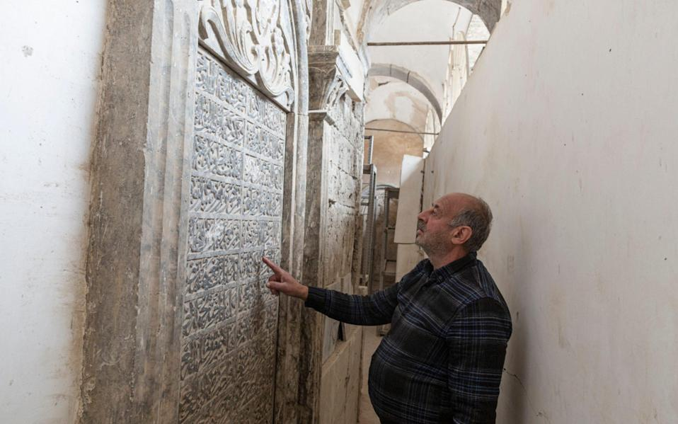 Saadullah Rassam, 63, who claims to be the only Christian currently living in the Old City of Mosul, looks at calligraphy inscribed on a tomb, in The Immaculate Syriac Catholic Church, in Mosul, Iraq, on March 4th 2021. - Sam Tarling for The Telegraph