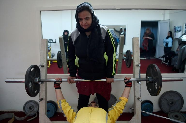 Parhiz helps teammate Sadya Ayubi with a bench press exercise