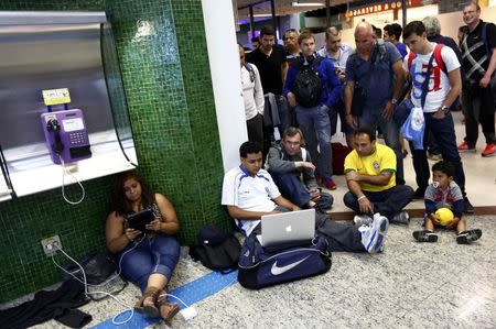 Waiting passengers gather around a laptop to watch the World Cup soccer match between Mexico and Cameroon at the domestic flight terminal of the airport in Sao Paulo, June 13, 2014. REUTERS/Kai Pfaffenbach