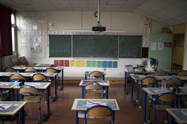 Desks marked with signs to enforce social distancing measures are pictured at the Saint-Tronc Castelroc primary school, which will begin to receive students on a voluntary basis, in Marseille, southern France, Monday, May 11, 2020. France is beginning to reopen Monday after two months of virus confinement measures. Shops, hair salons and some other businesses are reopening Monday and French citizens no longer need a special permission form to leave the house. (AP Photo/Daniel Cole)