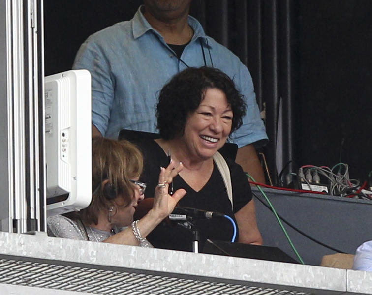Supreme Court Justice Sonia Sotomayor waves from a radio booth during the sixth inning of the baseball game between the New York Yankees and the Baltimore Orioles Wednesday, Aug. 1, 2012 at Yankee Stadium in New York. (AP Photo/Seth Wenig)
