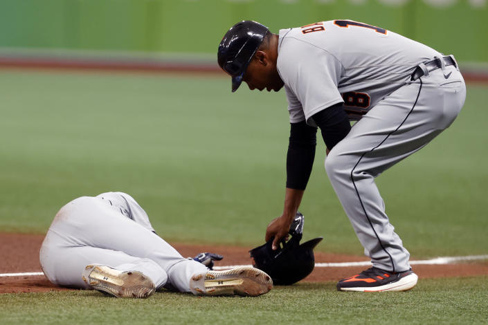 Detroit Tigers' Derek Hill lays on the field as first base coach Kimera Bartee leans over during the fifth inning of a baseball game against the Tampa Bay Rays Saturday, Sept. 18, 2021, in St. Petersburg, Fla. (AP Photo/Scott Audette)