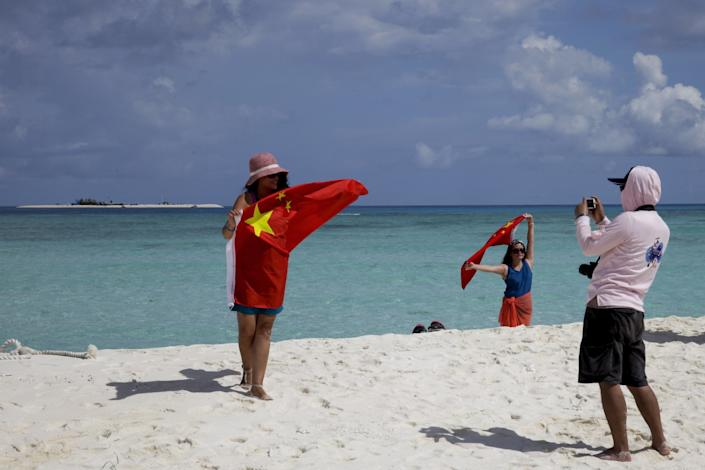 People hold the red Chinese flag on a white-sand beach