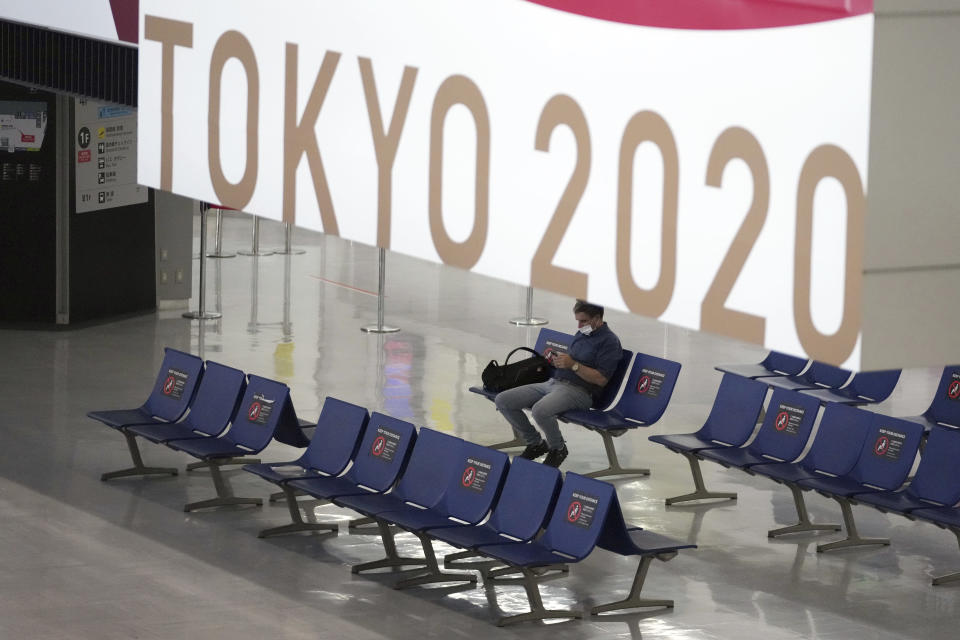 A man wearing a protective mask to help curb the spread of the coronavirus pauses near a banner of Tokyo 2020 Olympic at Narita International Airport Tuesday afternoon, June 1, 2021, in Narita, east of Tokyo. A state of emergency in Tokyo, Osaka and other prefectures was last week extended until June 20 as COVID-19 cases continue to put the medical system under strain.(AP Photo/Eugene Hoshiko)