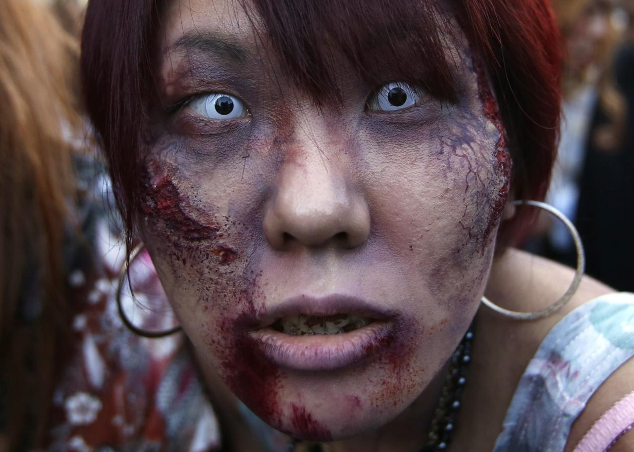 "A participant dressed as a zombie marches during a Halloween event to promote the U.S. TV series ""The Walking Dead"" at Tokyo Tower October 31, 2013. More than a thousand people dressed as zombies participated in the event to simulate taking over the tower, according to organisers. REUTERS/Issei Kato (JAPAN - Tags: ENTERTAINMENT SOCIETY)"