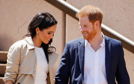 Britain's Prince Harry and wife Meghan, Duchess of Sussex share a moment as they walk during a visit at the Sydney Opera House in Sydney, Australia October 16, 2018. REUTERS/Phil Noble