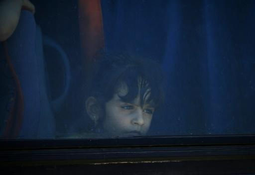 A Syrian girl looks out of a bus window during the evacuation of rebels and their families from Daraa city on July 15, 2018