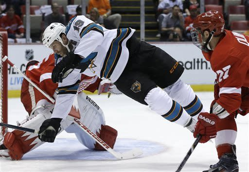 San Jose Sharks center Joe Thornton is tripped up in front of Detroit Red Wings goalie Jimmy Howard during the first period of an NHL hockey game in Detroit, Thursday, April 11, 2013. (AP Photo/Carlos Osorio)