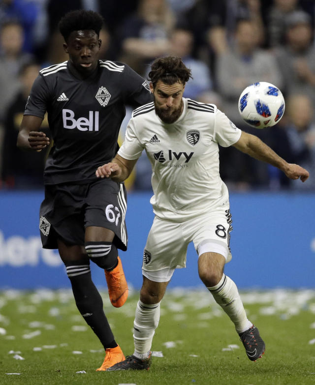 Vancouver Whitecaps forward Alphonso Davies (67) and Sporting Kansas City midfielder Graham Zusi (8) chase the ball during the first half of an MLS soccer match in Kansas City, Kan., Friday, April 20, 2018. (AP Photo/Orlin Wagner)