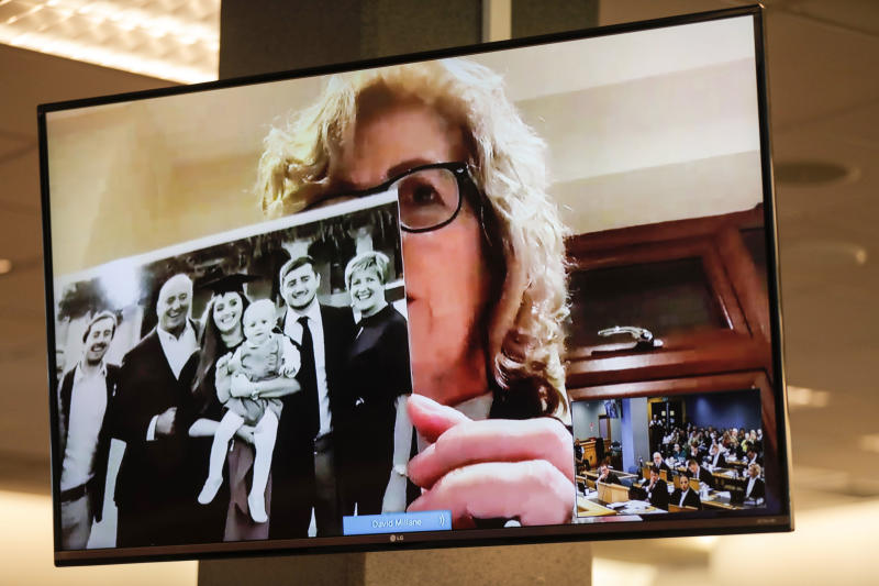 Gillian Millane, mother of murdered British backpacker Grace, holds up a photo during her victim impact statement via video link from England, at the sentencing of the man found guilty of her murder at the Auckland High Court in Auckland, New Zealand, Friday, Feb. 21, 2020. The killer, who has name suppression, has been sentenced to life imprisonment with a minimum non-parole period of 17 years. (Dean Purcel/New Zealand Herald via AP)