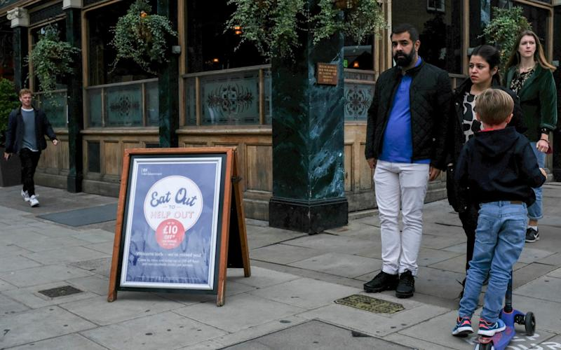 A 'Eat out to help out' sign stands outside a pub in the area of Notting Hill, in London, Monday, Aug. 31, 2020. - Alberto Pezzali/AP