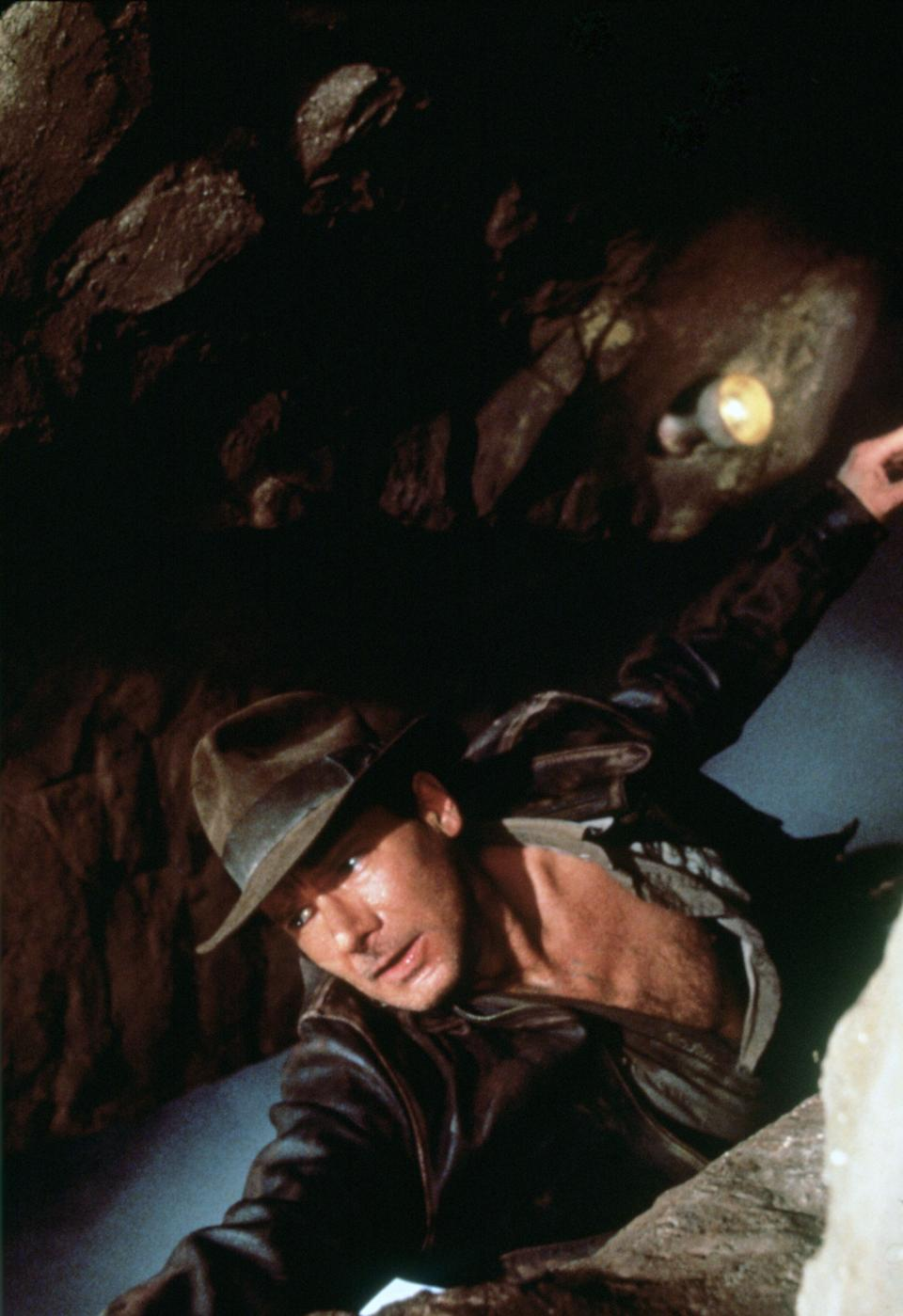 American actor Harrison Ford as the eponymous archaeologist in a scene from the film 'Indiana Jones and the Last Crusade', 1989. Here he hangs from the edge of a ravine while the Holy Grail falls past him into the abyss.  (Photo by Murray Close/Getty Images)