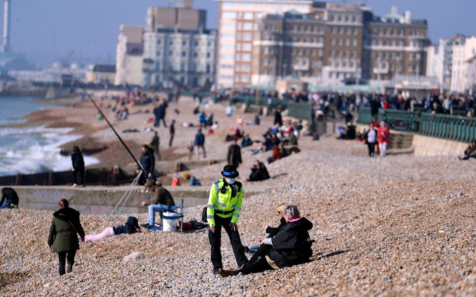 A community support officer speaks to people enjoying the sunshine on Brighton beach in Sussex in Sunday - PA/Steve Parsons