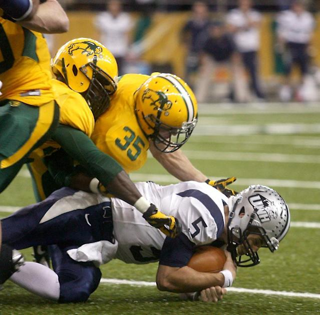 New Hampshire quarterback Sean Goldrich (5) is sacked by North Dakota State defender Christian Dudzik (35) during the first half of an NCAA college championship subdivision semifinal football playoff game, Friday, Dec. 20, 2013, at the Fargodome in Fargo, N.D. (AP Photo/Bruce Crummy)