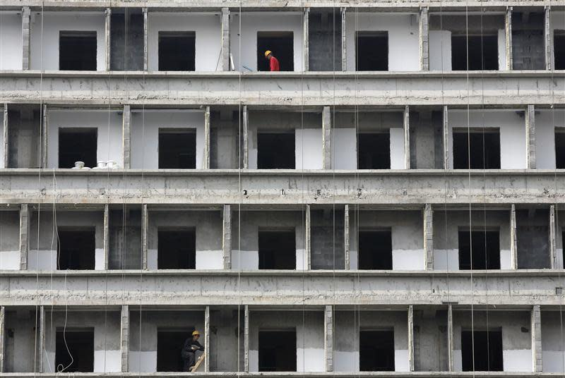 Workers labour at a construction site of new commercial building in Beijing