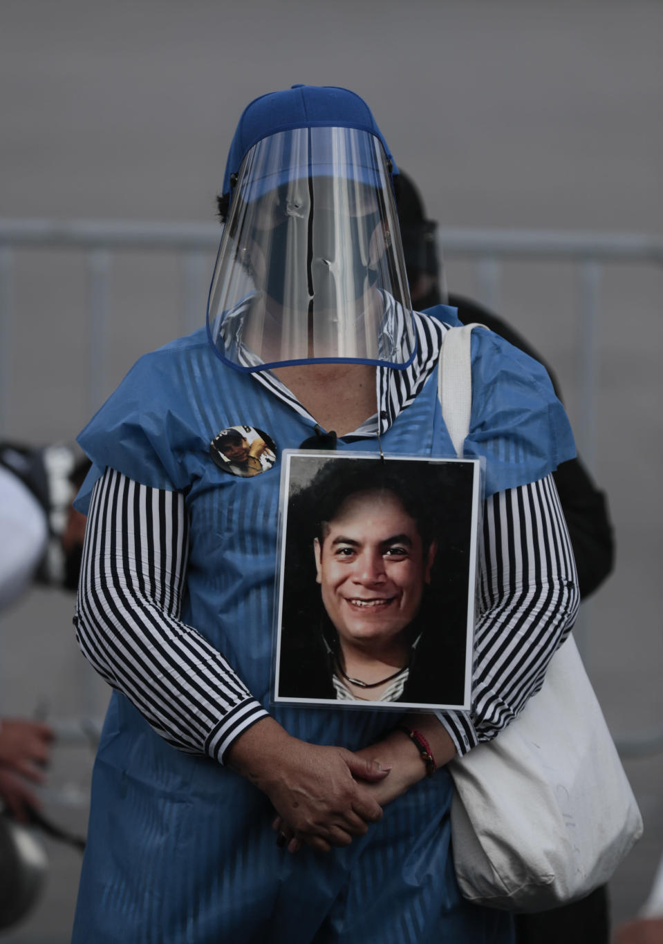 A woman wearing a mask amid the new coronavirus pandemic holds an image of a person who was disappeared, during a protest in front of the National Palace in Mexico City, Thursday, June 4, 2020. Relatives of different groups searching for the disappeared protested the cut to the budget destined for their search. (AP Photo/Eduardo Verdugo)