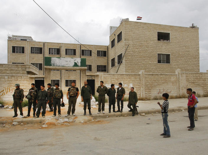 In this picture taken during a UN observer-organized tour, Syrian boys, right, look at Syrian army soldiers, left, as they stand outside a school building used as a temporary military base in Hama city, central Syria, on Thursday, May 3, 2012. Syrian security forces stormed dorms at a northwestern university to break up anti-government protests there, killing at least four students and wounding several others with tear gas and live ammunition, activists and opposition groups said Thursday. (AP Photo/Muzaffar Salman)