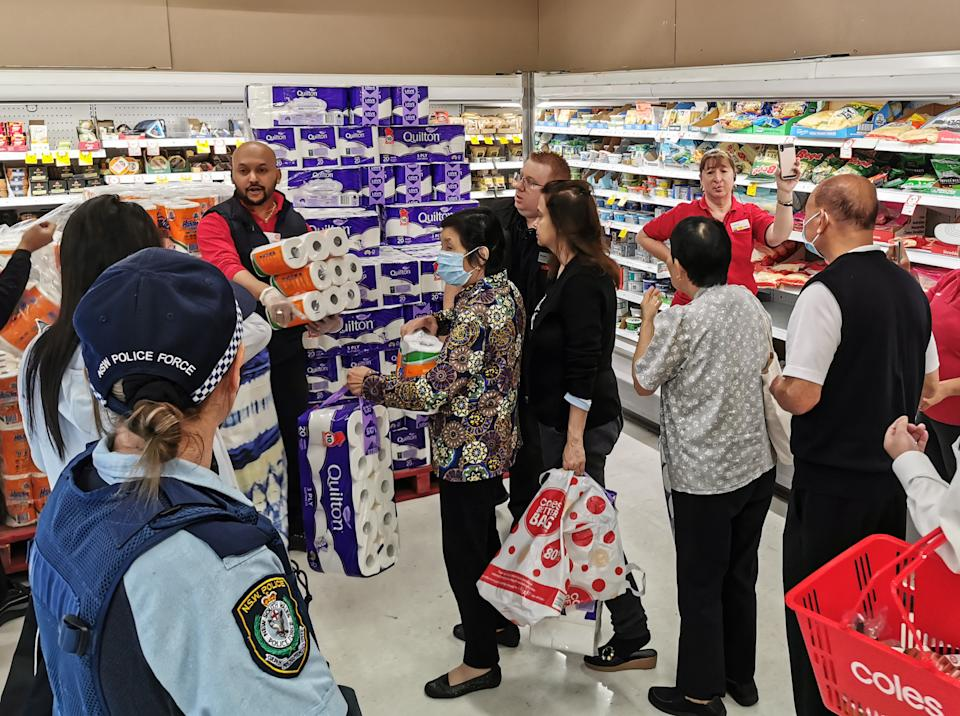 People receiving toilet paper, paper towel and pasta as a police officer watches on at Coles Supermarket, Epping in Sydney. Source: AAP