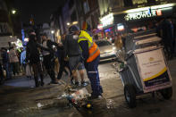 A street cleaner sweeps a street in Soho as late-night drinkers continue into the early hours of Sunday morning as coronavirus lockdown restrictions are eased across England, Sunday July 5, 2020. (Victoria Jones/PA via AP)