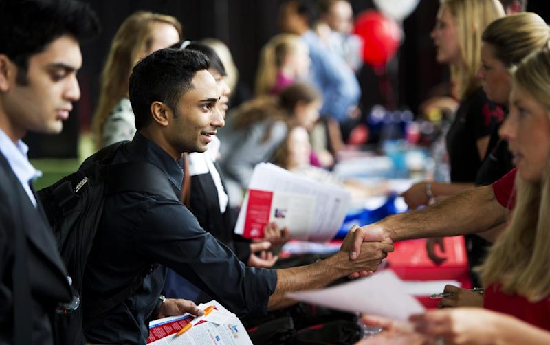 This Sept. 26, 2012 photo provided by Northeastern University in Boston shows student Azan Morani, left, shaking hands with a Johnson & Johnson representative at a Co-op Networking Expo on campus featuring companies looking to hire co-op students. Northeastern's ranking among colleges has improved in the last few years and applications have soared, partly due to the popularity of its co-op program, which offers every student several semesters of work experience. College programs that emphasize career preparation are in greater demand since the recession. (AP Photo/Northeastern University, Brooks Canaday)