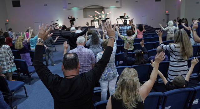 <p>Members of the Dayspring Church raise their hands in prayer Sunday, May 20, 2018, in Santa Fe, Texas. A gunman opened fire inside Santa Fe High School Friday, May 18, 2018, killing at least 10 people. (Photo: David J. Phillip/AP) </p>