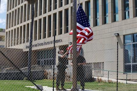 U.S. Marines raise the U.S. flag at half-staff at the U.S. Embassy in Havana