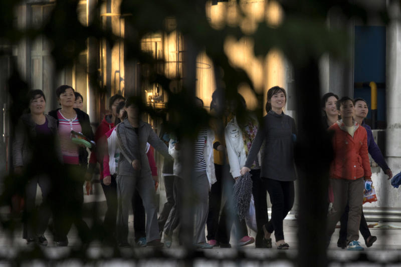 In this Aug. 31, 2017, photo, North Korean workers walk in a group to dormitories in the compound of the seafood processing factory Hunchun Pagoda in the city of Hunchun in northeastern China's Jilin province. Roughly 3,000 North Koreans are believed to work in Hunchun, a far northeast Chinese industrial hub just a few miles from the borders of both North Korea and Russia. The workers are paid a fraction of their salaries, while the rest - as much as 70 percent - is taken by North Korea's government. (AP Photo/Ng Han Guan)