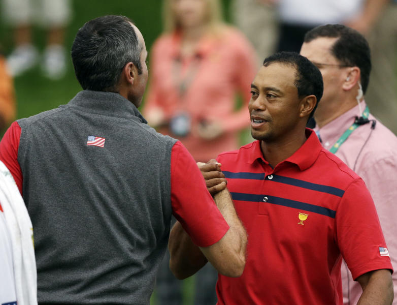 United States team player Tiger Woods, right, and Matt Kuchar celebrate after defeating International team player Louis Oosthuizen, of South Africa, and Charl Schwartzel, of South Africa, in the foursome match at the Presidents Cup golf tournament at Muirfield Village Golf Club Saturday, Oct. 5, 2013, in Dublin, Ohio. (AP Photo/Darron Cummings)