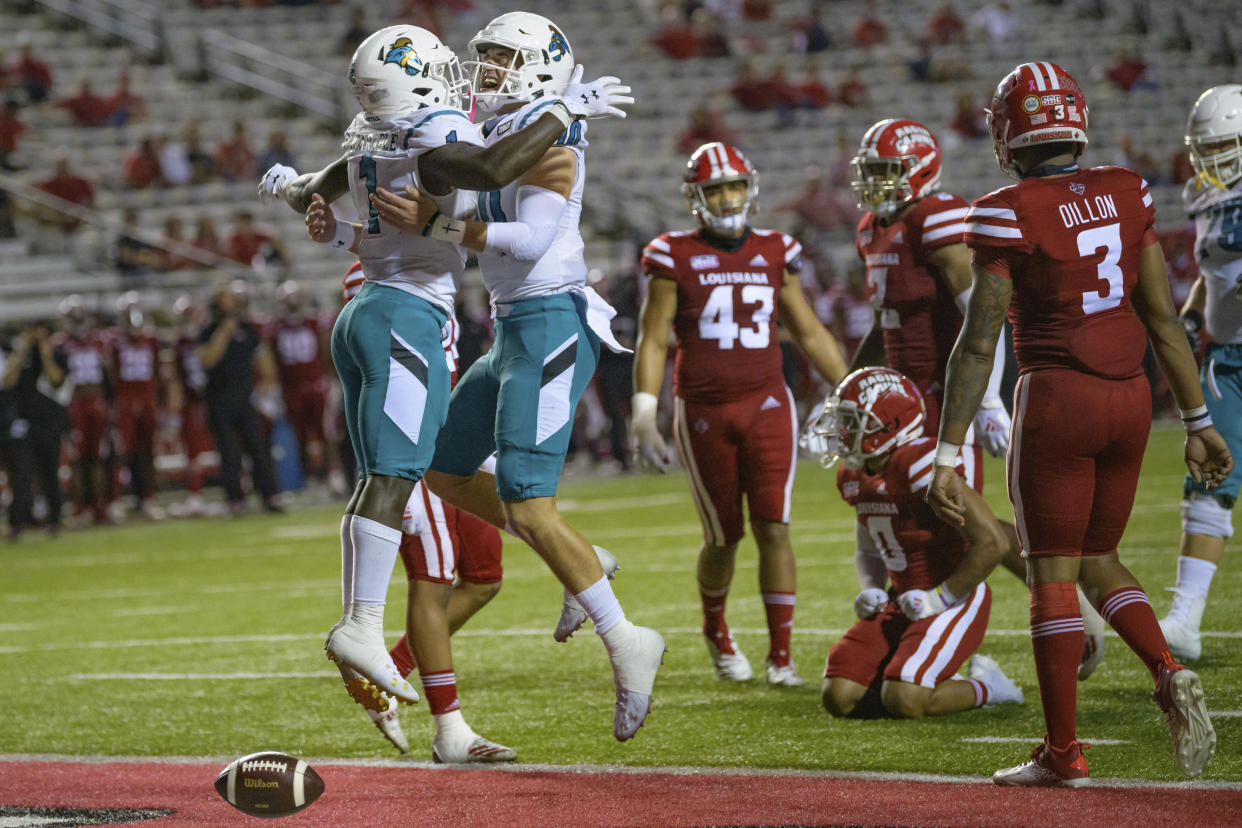 FILE - In this Oct. 14, 2020, file photo, Coastal Carolina running back CJ Marable (1) celebrates a touchdown with quarterback Grayson McCall (10) during an NCAA football game against Louisiana-Lafayette in Lafayette, La. Coastal Carolina coach Jamey Chadwell sees a new challenge for his surprising Chanticleers this fall: staying as hungry at chasing success as they were during their landmark 2020 season. Coastal Carolina is ranked No. 22 in the preseason this year, are not alone in the AP Top 25 with Louisiana-Lafayette right behind them at No. 23. It's the first time the league has had a pair of teams in the preseason rankings. (AP Photo/Matthew Hinton, File)