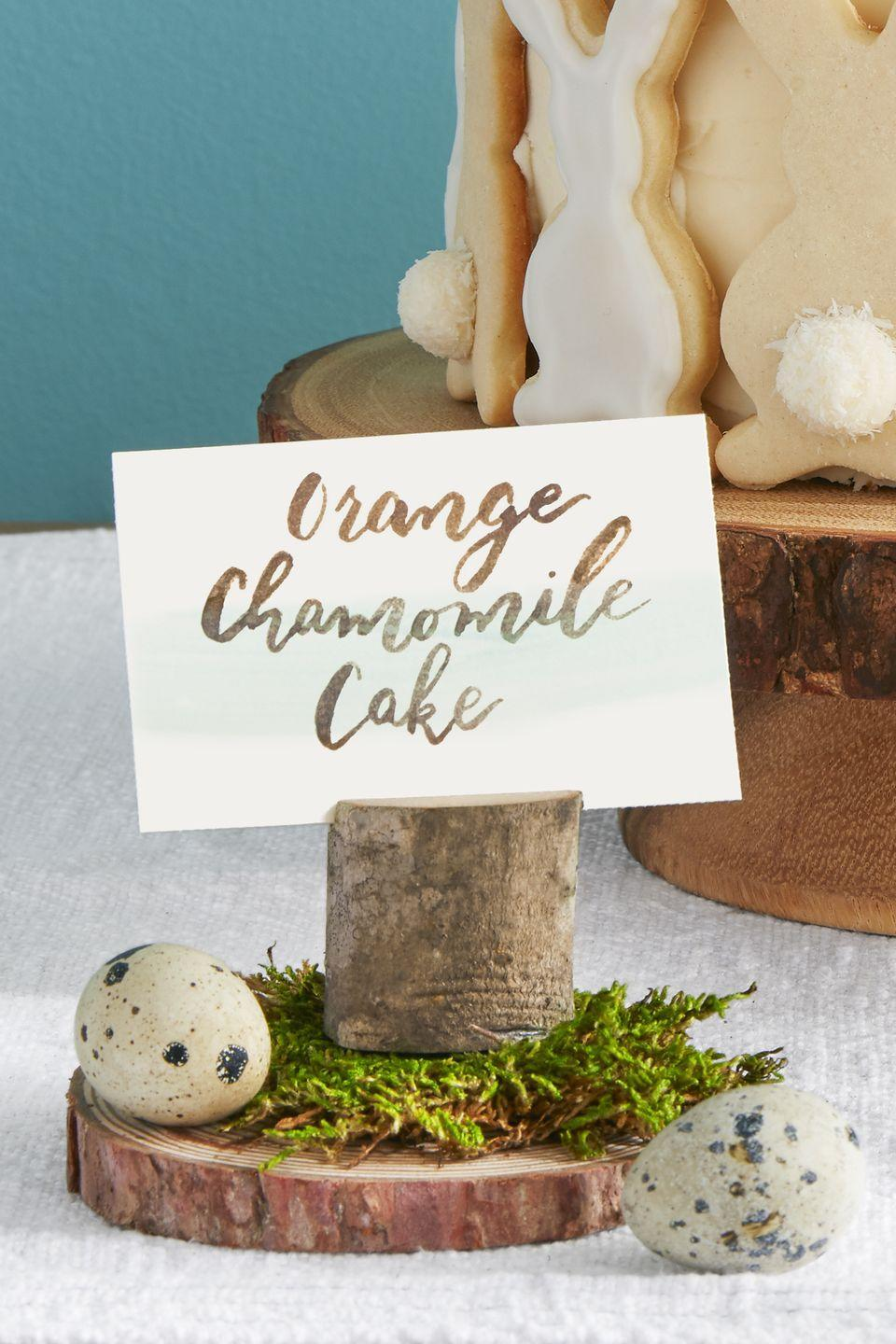"<p>Add some pizzazz to your holiday buffet or food table with some rustic branches fashioned together to display the names of your dishes. Craft these pieces by cutting a thin sliver in a small piece of wood; place atop wood round and add moss and eggs.</p><p><a class=""link rapid-noclick-resp"" href=""https://www.amazon.com/Assorted-Natural-Hanging-Decorations-Ornaments/dp/B01FRDI8EY/ref=sr_1_2?tag=syn-yahoo-20&ascsubtag=%5Bartid%7C10050.g.1652%5Bsrc%7Cyahoo-us"" rel=""nofollow noopener"" target=""_blank"" data-ylk=""slk:SHOP WOOD ROUND"">SHOP WOOD ROUND</a></p>"