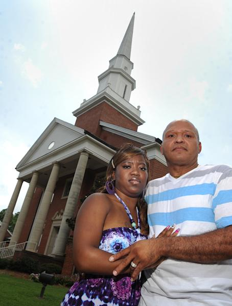 In this July 27, 2012 photo, Charles, right, and Te'Andrea Wilson pose for photos in front of the First Baptist Church in Crystal Springs, Miss. Just days before they were to be wed at the church, the Wilsons were told the wedding would not be permitted because some members of the congregation didn't want a black couple to be married there. The couple had been attending the church and had plans to join. The wedding was moved to a nearby church and officiated by the First Baptist pastor, Rev. Stan Weatherford. (AP Photo/The Clarion-Ledger, Barbara Gauntt) NO SALES