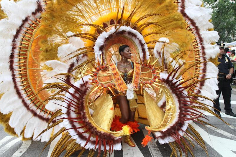 Dressed in costume, Kelva Joseph makes her way along Eastern Parkway in the Brooklyn borough of New York during the West Indian Day Parade, Monday, Sept. 2, 2013. (AP Photo/Tina Fineberg)