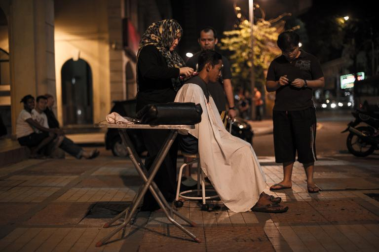 Azmina Burhan cuts the hair of a homeless person in downtown Kuala Lumpur, on November 13, 2013