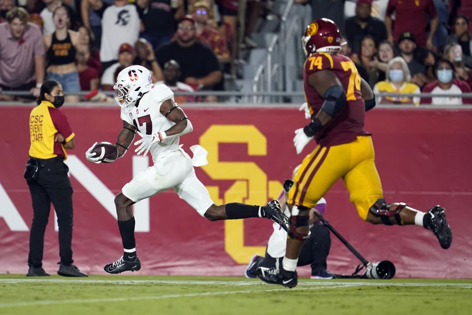 Stanford cornerback Kyu Blu Kelly, left, returns an interception for a touchdown during the second half of the team's NCAA college football game against Southern California on Saturday, Sept. 11, 2021, in Los Angeles. (AP Photo/Marcio Jose Sanchez)