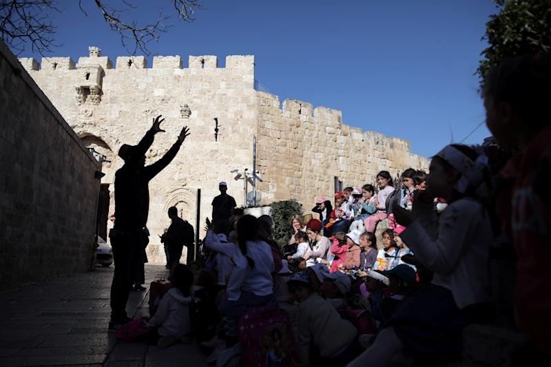 A man is silhouetted as he speaks to a group of children near Zion Gate in Jerusalem's Old City. (Photo: Nir Elias/Reuters)