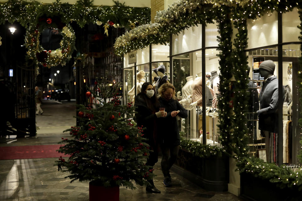 FILE - In this Wednesday, Nov. 25, 2020 file photo, women wearing face masks walk past a Christmas tree and lights in Burlington Arcade, where all non-essential shops are temporarily closed during England's second coronavirus lockdown, in London. Nations are struggling to reconcile cold medical advice with a holiday tradition that calls for big gatherings in often poorly ventilated rooms, where people chat, shout and sing together, providing an ideal conduit for a virus that has killed over 350,000 people in Europe so far. (AP Photo/Matt Dunham, File)