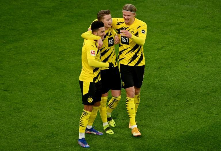 Jadon Sancho (L) celebrates his goal against Augsburg with Dortmund team-mates Marco Reus (C) and Erling Braut Haaland